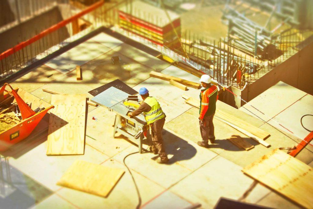 Arbeiter auf Baustelle mit Bauzaunbanner im Hintergrund